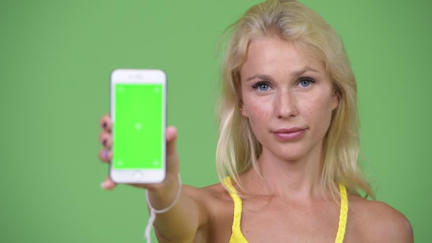 Young happy beautiful blonde woman showing phone | Shutterstock HD Video #1015764979