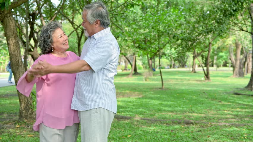 Sweet senior couple dancing in park. Old asian man and woman dancing together in park standing up. Senior lifestyle concept. | Shutterstock HD Video #1015773949