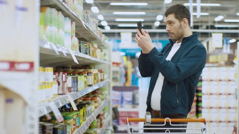 At the Supermarket: Handsome Man Uses Smartphone and Takes Picture of the Can of Goods. He's Standing with Shopping Cart in Canned Goods Section. Shot on RED EPIC-W 8K Helium Cinema Camera.