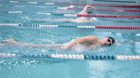 Slow motion swimmer competition or training at swimming pool