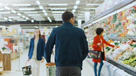 At the Supermarket: Man Pushing Shopping Cart Through Fresh Produce Section of the Store. Store with Many Customers Shopping. Following Back View Shot. Shot on RED EPIC-W 8K Helium Cinema Camera.