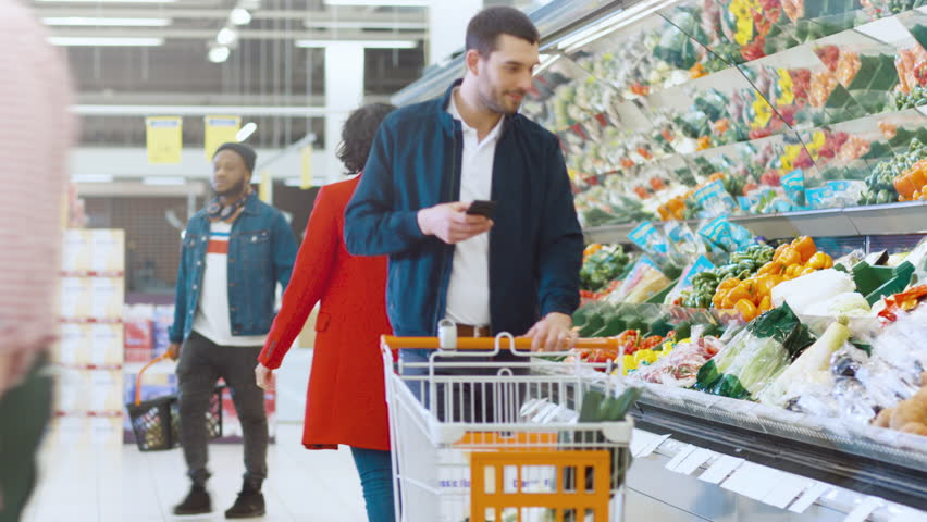 At the Supermarket: Handsome Young Man Uses Smartphone while Pushing Shopping Cart and Choosing Vegetables in Fresh Produce Section. Other Customers in the Background. Shot on RED EPIC-W 8K. | Shutterstock HD Video #1015805299