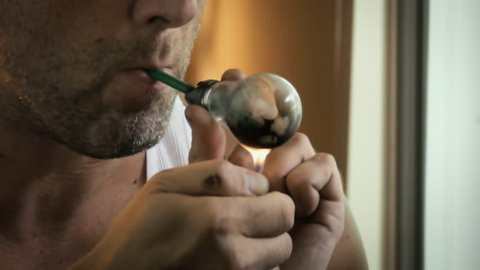 Addict smoking crystal meth or other illegal drug from lightbulb pipe close up
