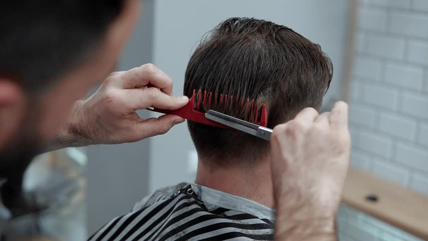 Close-up of barber cuts the hair by scissors at barbershop. Hairdresser's hands at working process. Barber making haircut of attractive bearded man in barbershop. Hairdresser at work. Beauty saloon.   Shutterstock HD Video #1015820479