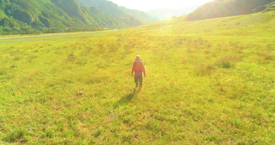 Aerial 4K UHD view. Low altitude flight over young man tourist walking across green mountain field. Huge rural valley and sunny meadow at summer day. Backpack hiking guy. | Shutterstock HD Video #1015837219
