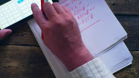 economic settlement-business concept. men's hands,calculator,notebook and  marker on a wooden table.Closeup.view from above