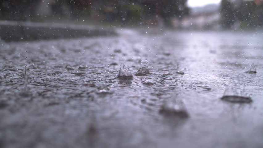 SLOW MOTION CLOSE UP: Autumn rain water drops falling into big puddle on asphalt, flooding the street. Road floods due to the heavy rain in wet season. Raindrops falling down onto submerged road #1015854739