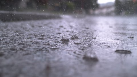 SLOW MOTION CLOSE UP: Autumn rain water drops falling into big puddle on asphalt, flooding the street. Road floods due to the heavy rain in wet season. Raindrops falling down onto submerged road