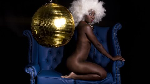 beautiful african female dancer with large afro wig posing in blue leather chair under a disco ball. Perfect for stylish club, disco and fashion events
