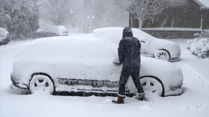 Man Shoveling Snow off Car