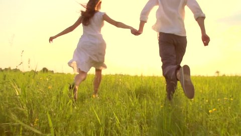 Happy young couple holding hands run through a wide field, having fun outdoors. Countryside. Man and woman running away on the meadow. Happy joyful family outdoor. Sun flare. Slow motion Full HD 1080p