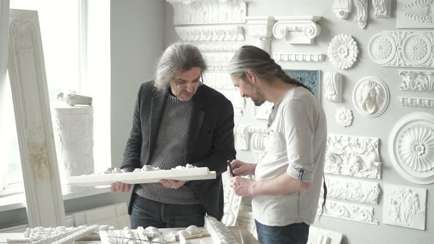 Two men designers discussing molding with flower ornament in bright studio and smiling. Indoors. | Shutterstock HD Video #1015871179