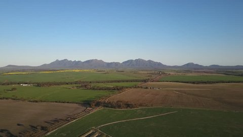 Aerial panoramic view of the scenic mountains of the Stirling Range National Park in Western Australia, flying above a wide open plain of agricultural fields on a sunny day with blue sky.
