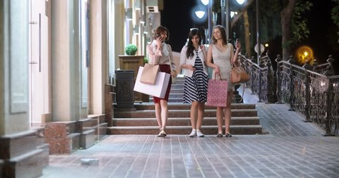 Three female friends walking down broadway near shopping centers, with shopping bags in hands chatting, smiling, talking on phones, taking selfies 4k