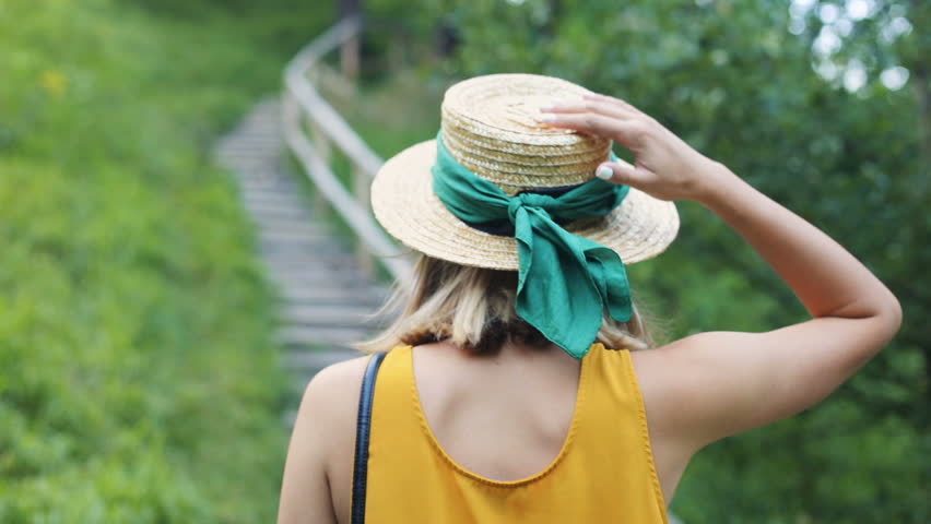 Nice young Caucasian woman wearing yellow t-shirt walking up the stairs. Slavic girl touching hat. Outdoors. Summertime. Back. | Shutterstock HD Video #1015902529