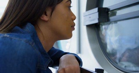 Thoughtful woman looking at washing machine at laundromat 4k