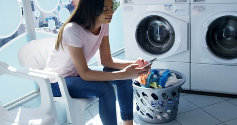 Young woman using mobile phone at laundromat 4k