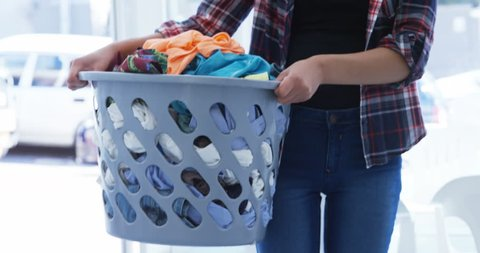 Mid section of woman carrying clothes in laundry basket at laundromat 4k