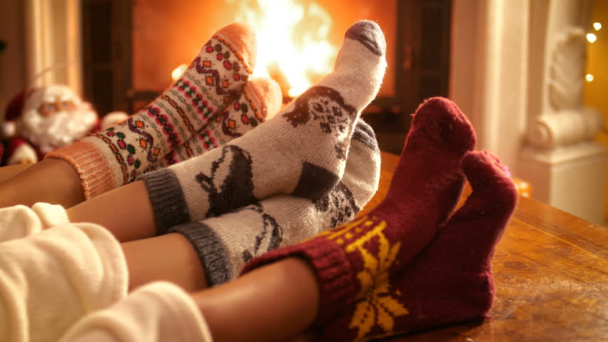 Closeup 4k footage of family with child wearing warm wool socks lying by the fireplace on Christmas eve | Shutterstock HD Video #1015934989