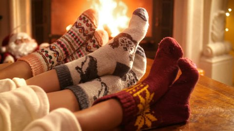 Closeup 4k footage of family with child wearing warm wool socks lying by the fireplace on Christmas eve