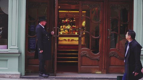 LONDON UK - MAY 21, 2018. Door man Fortnum & Mason open the door for people walking and out the mall in London