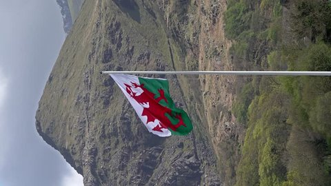 Welsh flag waving in the beautiful landscape of Llanberis, Snowdonia in Wales at the lake padarn.