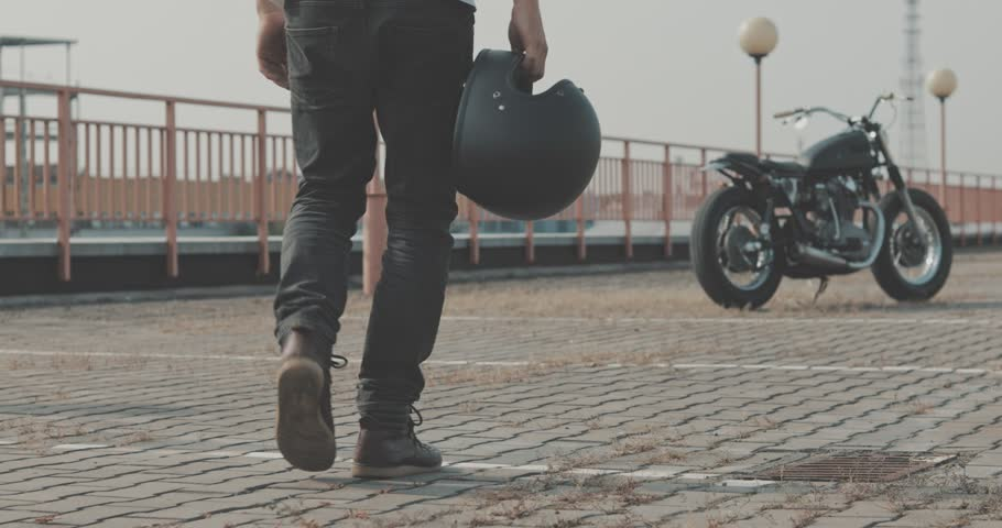 Biker guy walking through parking to his motorcycle. Motorcyclist and vintage motorbike from 1970s . Back side view urban lifestyle scene. 4K video shooting by handheld gimbal