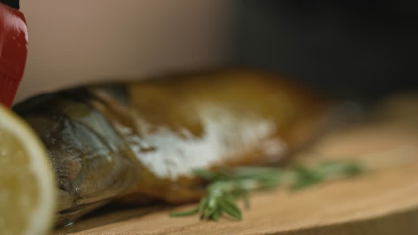 The chef smears smoked fish with oil before serving via silicone culinary brush. Restaurant or cafe kitchen. Wooden table, fish cooked in smokehouse, cutting board, leek, lemon, thyme. Macro shot | Shutterstock HD Video #1016047669