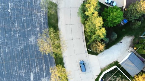 Car driving along the empty road trough american neighborhood. Flying above car traveling on street. Aerial view of road, residential houses. American suburb.