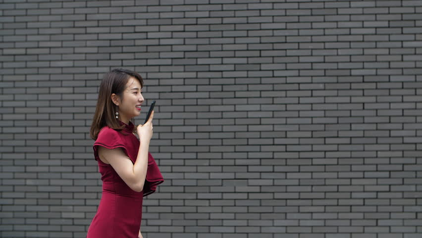 Pretty young asian woman using mobile phone walking in the street in slow motion | Shutterstock HD Video #1016057629