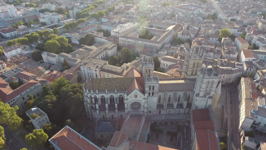 View from a drone flying around Montpellier cathedral during sunrise. France ecusson