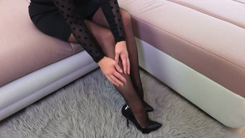 Woman sitting in bed and touching black hosiery