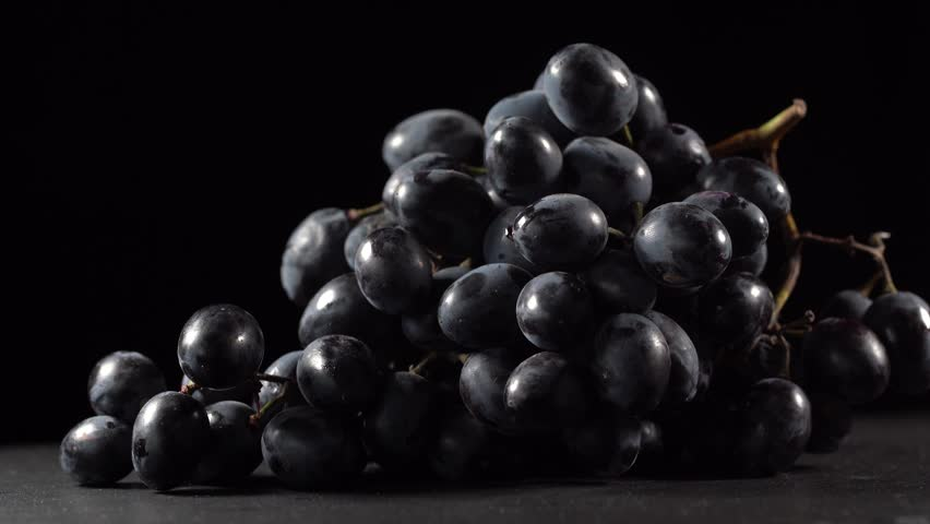 Bunches of ripe red grapes rotating on a black background, close up, macro