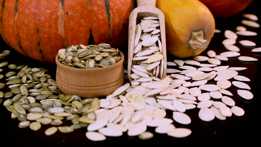 Autumn composition of pumpkin. White and green pumpkin seeds, orange and yellow squash. Black background