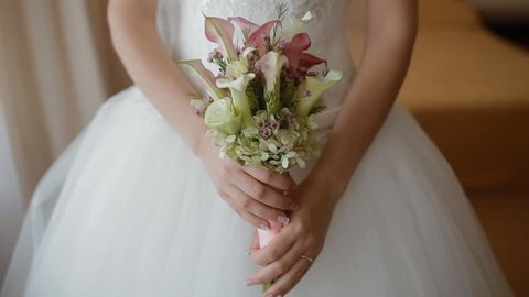 Bride holding wedding bouquet of white and pink calla near the hips