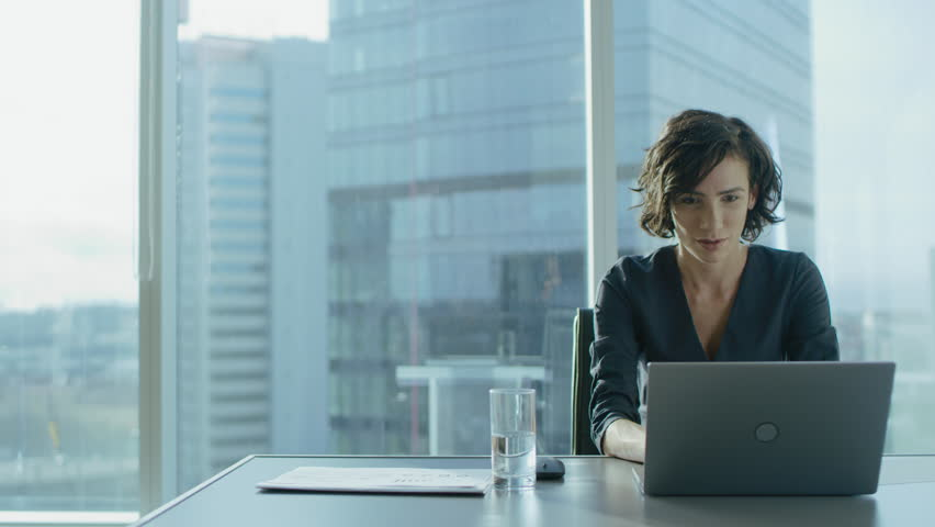 Beautiful Successful Businesswoman Working on a Laptop in Her Office with Cityscape View Window. Strong Independend Female CEO Runs Business Company. Shot on RED EPIC-W 8K Helium Cinema Camera. | Shutterstock HD Video #1016145739