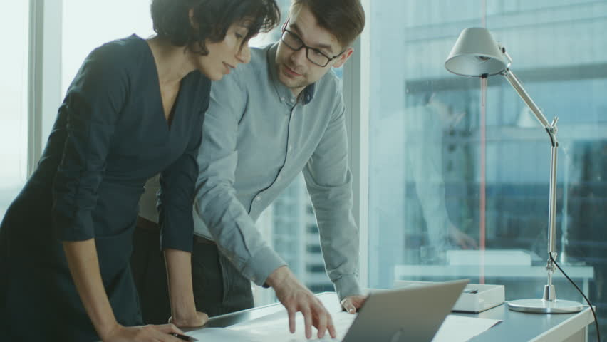Two Young Business Entrepreneurs Leaning on a Desk, Working with Documents for a New Startup Project. Businesspeople Using Laptop in the Office with Cityscape Window View. Shot on RED EPIC-W 8K. | Shutterstock HD Video #1016145889