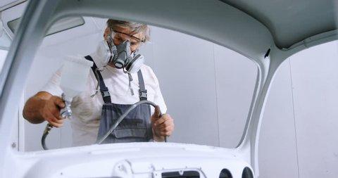 Male mechanic using spray paint in garage 4k