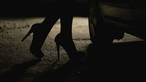 Silhouette of female legs in high heels coming to car, prostitution, sex tourism