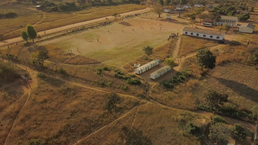 Slow Rising Shot Over a Soccer Game on a Dirt Field at a Rural Primary School in Zimbabwe, Africa to Reveal a Beautiful Mountain Landscape During Sunset #1016180029