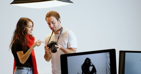 Male photographer and model discussing over photos in photo studio 4k