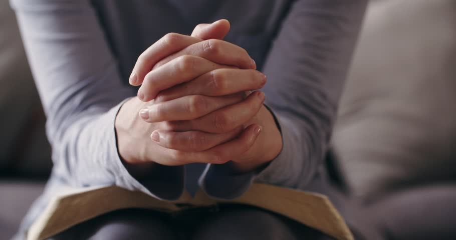 Bible study and Christianity concept - a handheld closeup shot of a woman praying over an open Bible while sitting on a couch at home. She closes the book after the prayer. | Shutterstock HD Video #1016239729