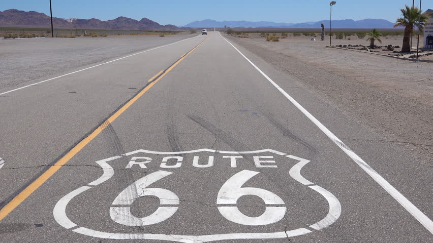 CIRCA 2018 - Establishing shot of a lonely desert highway in Arizona with Route 66 painted on the pavement. | Shutterstock HD Video #1016240179
