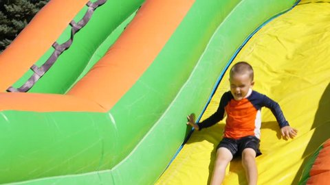 A slow motion shot of children playing and sliding down a large inflatable water slide