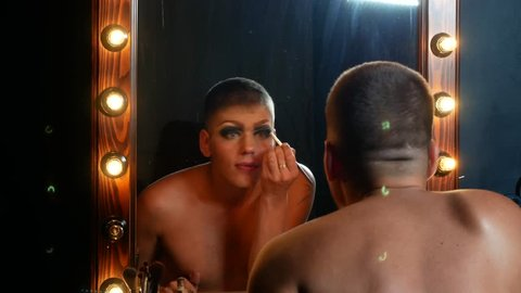 concept of travesty make-up. a handsome young man applies makeup on his face, sitting in front of a mirror in the dressing room. professional travesty artist. close-up, 4k.