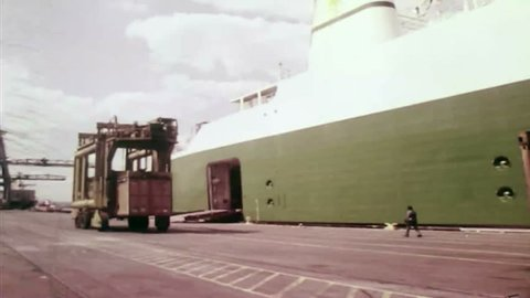 CIRCA 1970s - A straddle carrier is used to move intermodal containers to a cargo ship at the Port of New York and New Jersey.