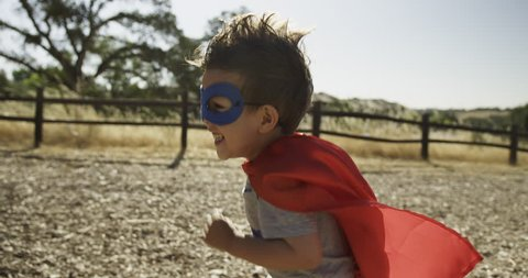 Little boy wearing a red cape and blue mask, playing superhero 4k, slow motion, stock footage,