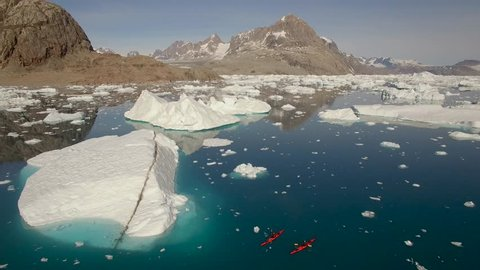 Greenland, aerials from kayaker paddling beneath icebergs