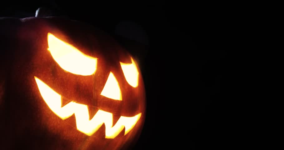 Shining Jack-O-Lantern. Halloween pumpkin with scary face smoke inside with flame isolated on the black background. | Shutterstock HD Video #1016310739