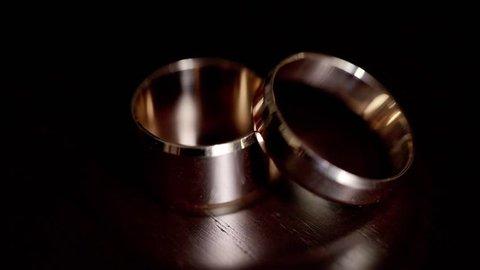 Wedding rings are not a dark table in the rays of light,two wedding rings in infinity sign. Love concept.